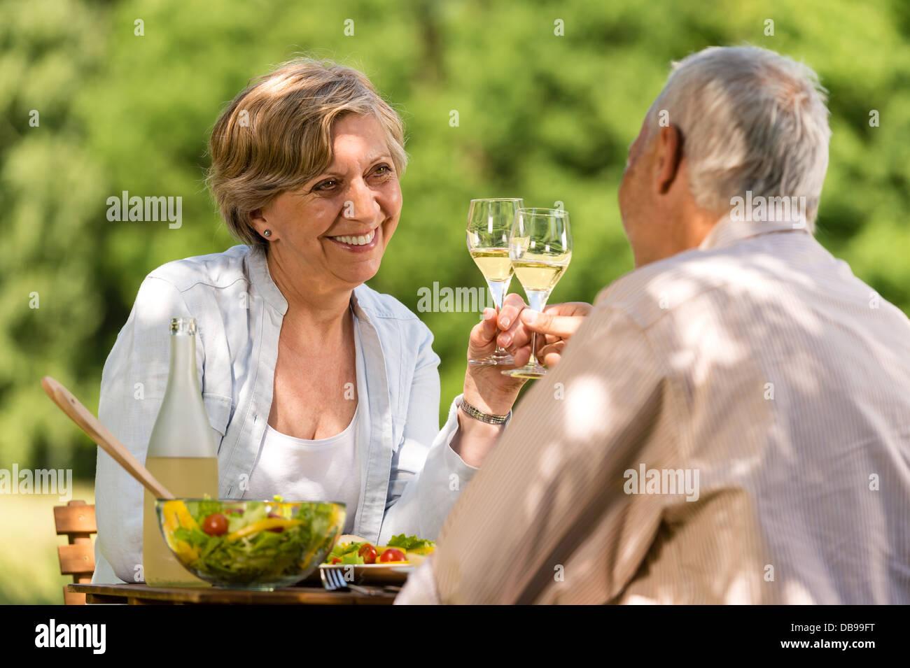 Heureux les personnes âgées clinking glasses in garden Photo Stock