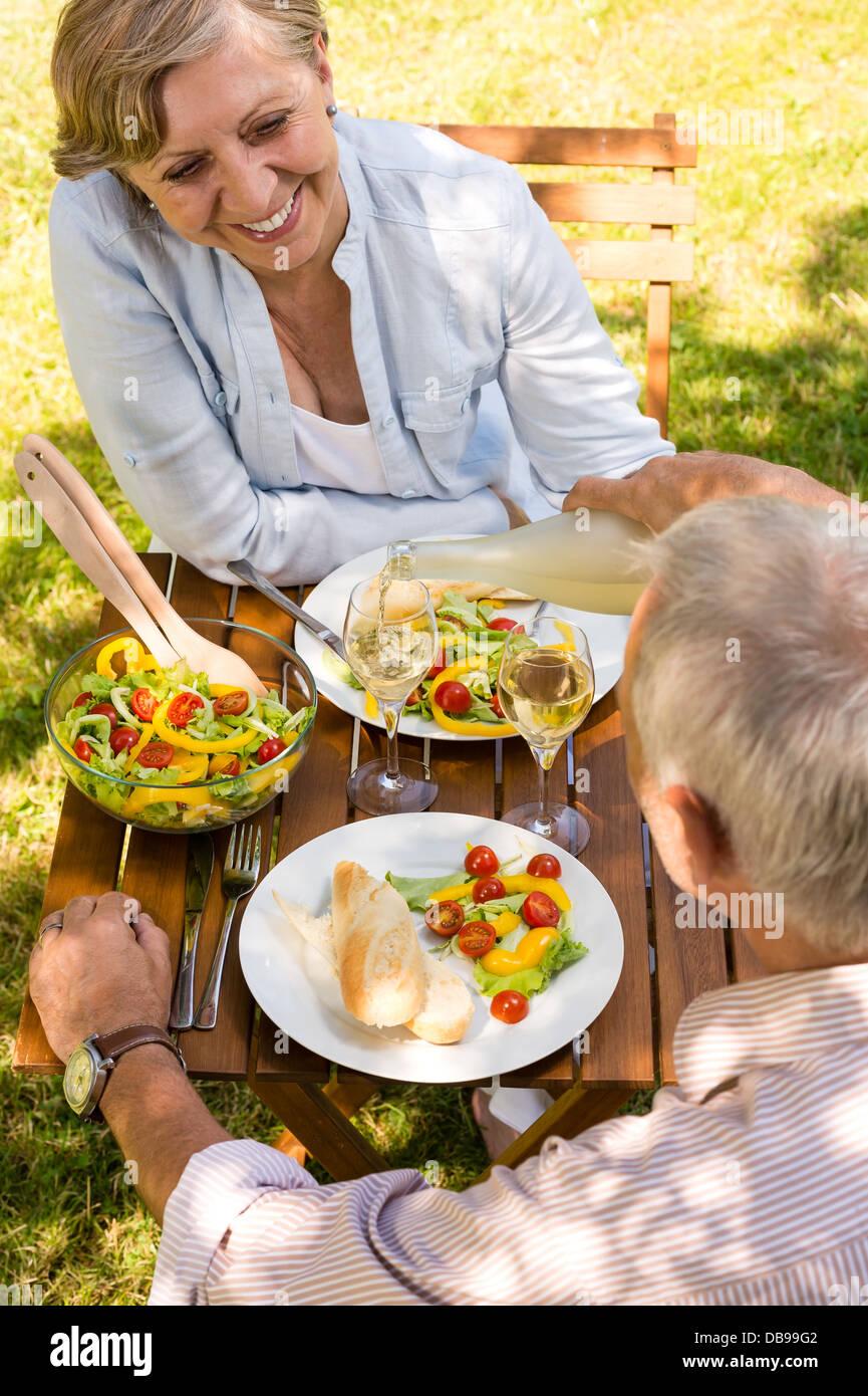 Smiling couple retraité boire et manger à l'extérieur Photo Stock