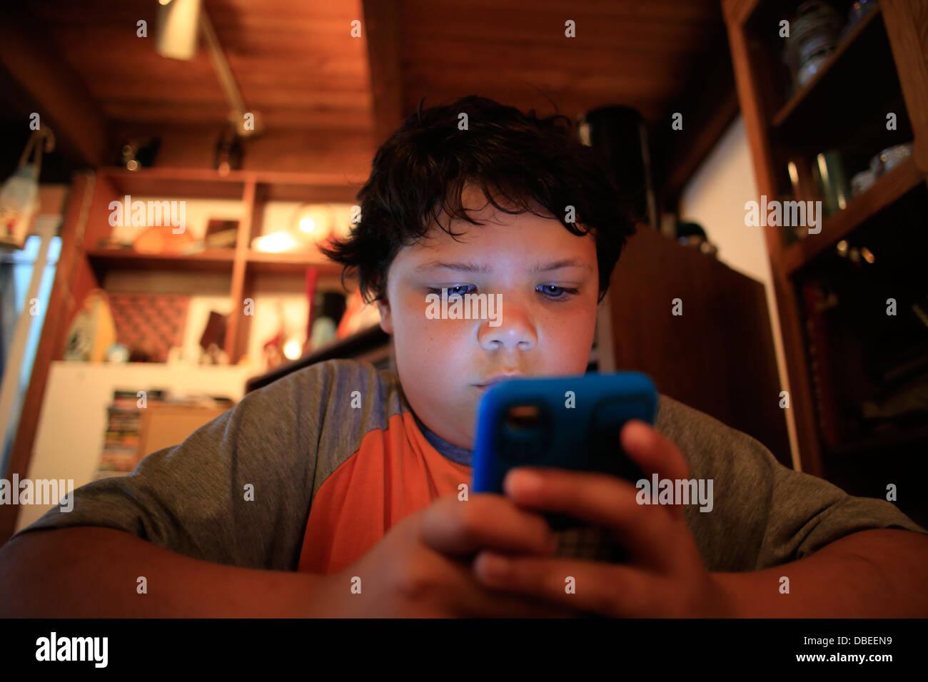 Un garçon de neuf ans à l'aide d'un IPOD Apple iPodTouch ou IPhone iPhone ou IPad portable media player Banque D'Images