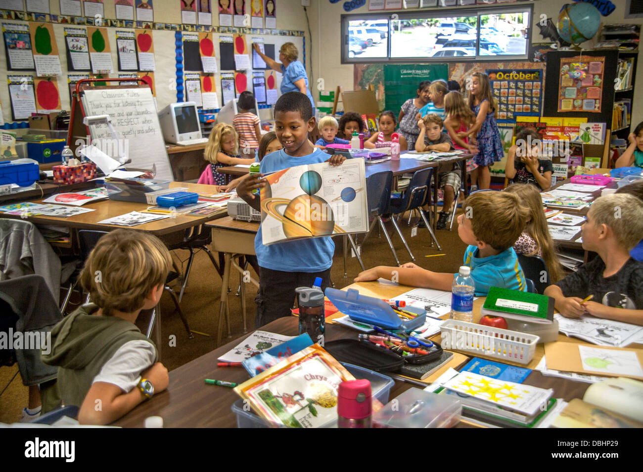 Un écolier du primaire utilise un livre d'astronomie illustré pour expliquer le système solaire Photo Stock