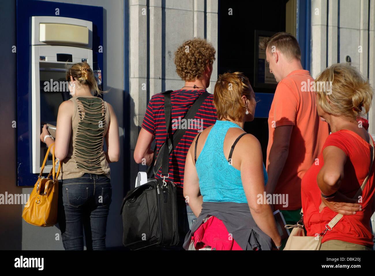 Les clients en attente dans la file d'attente pour recueillir de l'argent au distributeur Le distributeur Photo Stock
