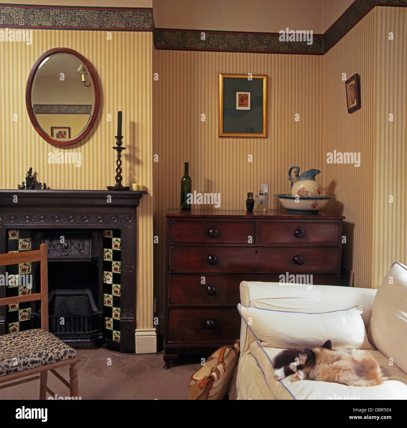miroir ovale au-dessus de cheminée en fonte dans la chambre avec