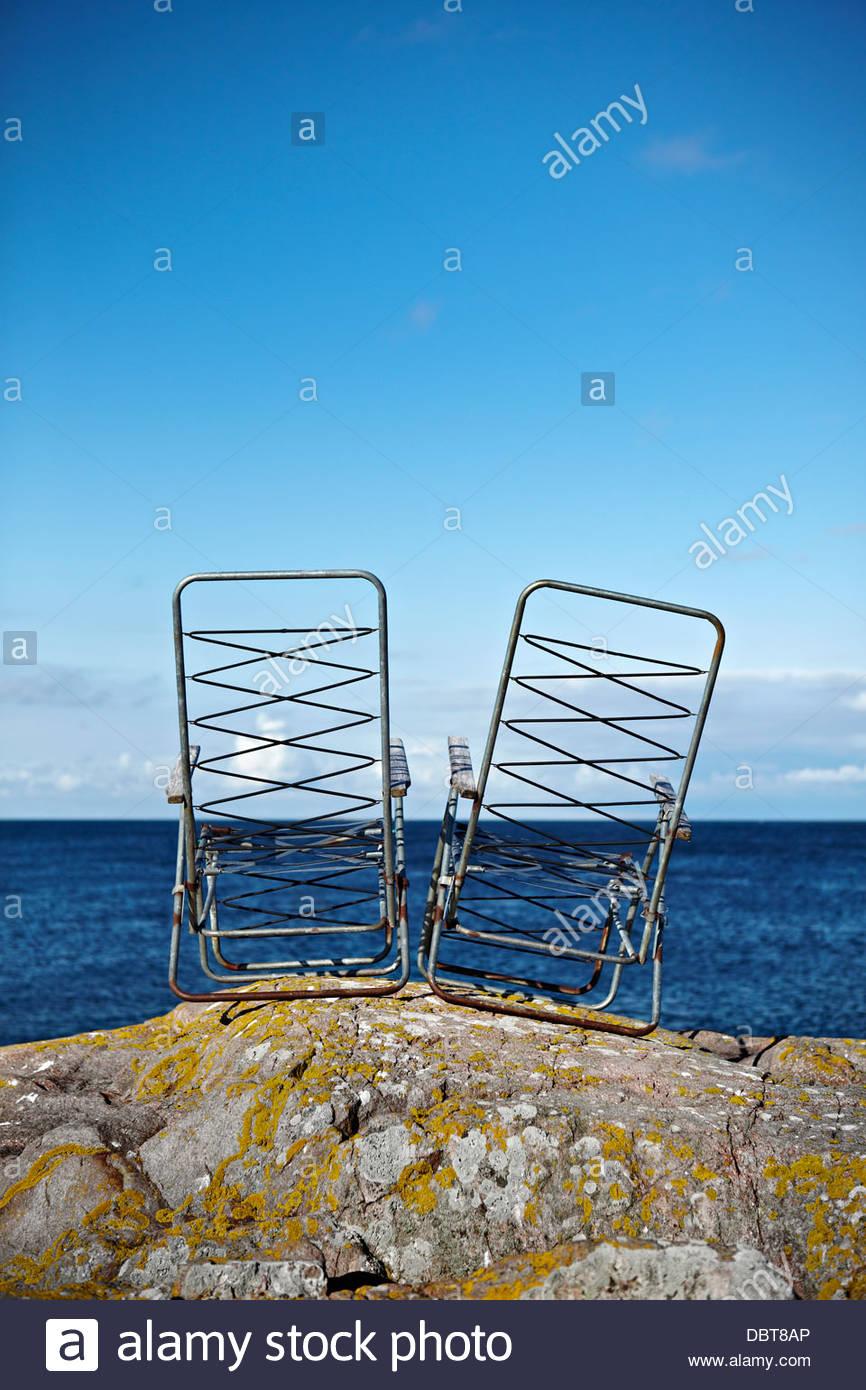 Deux chaises longues sur mer près de rock Photo Stock