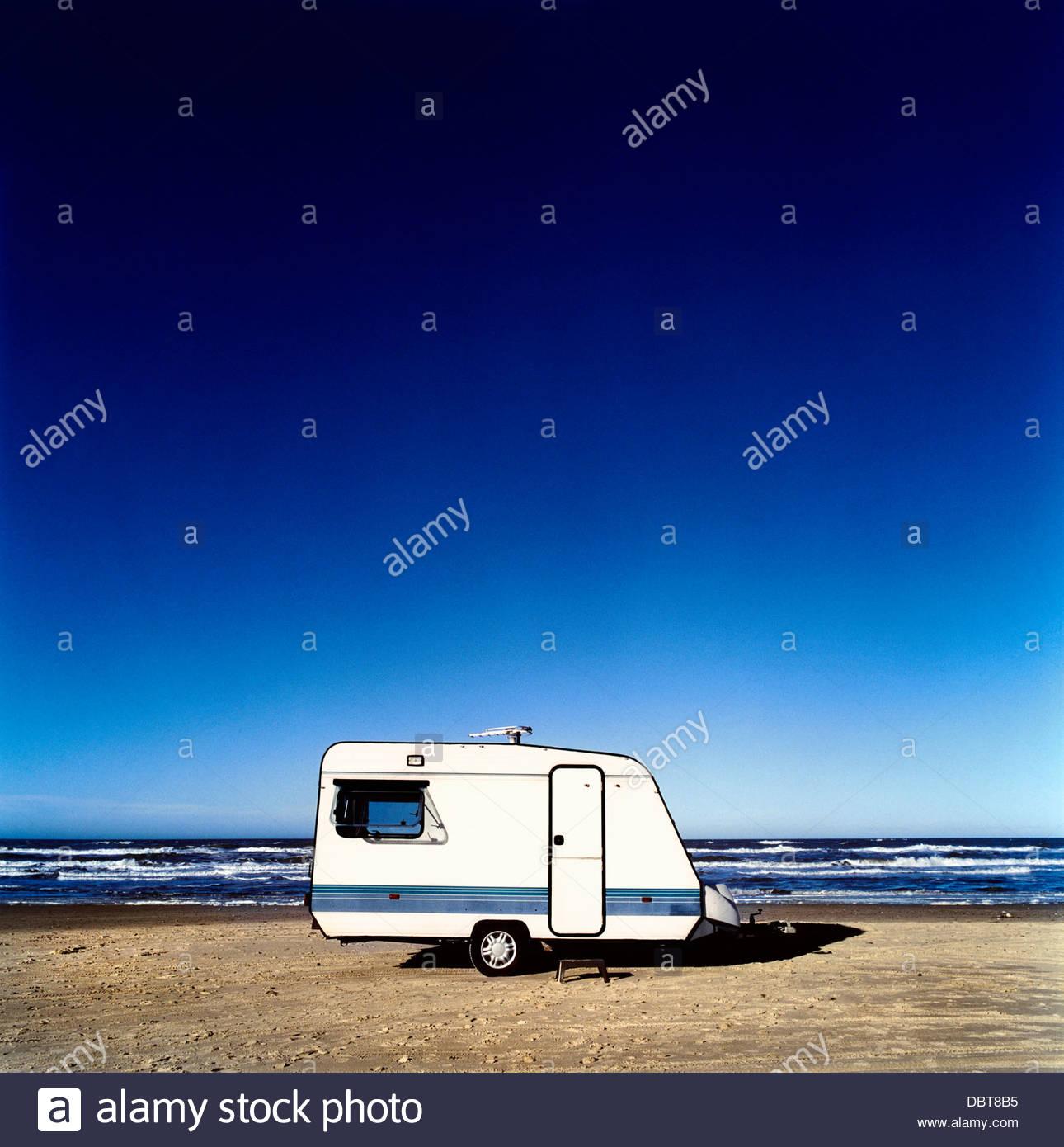 Caravane sur la plage contre le ciel bleu Photo Stock