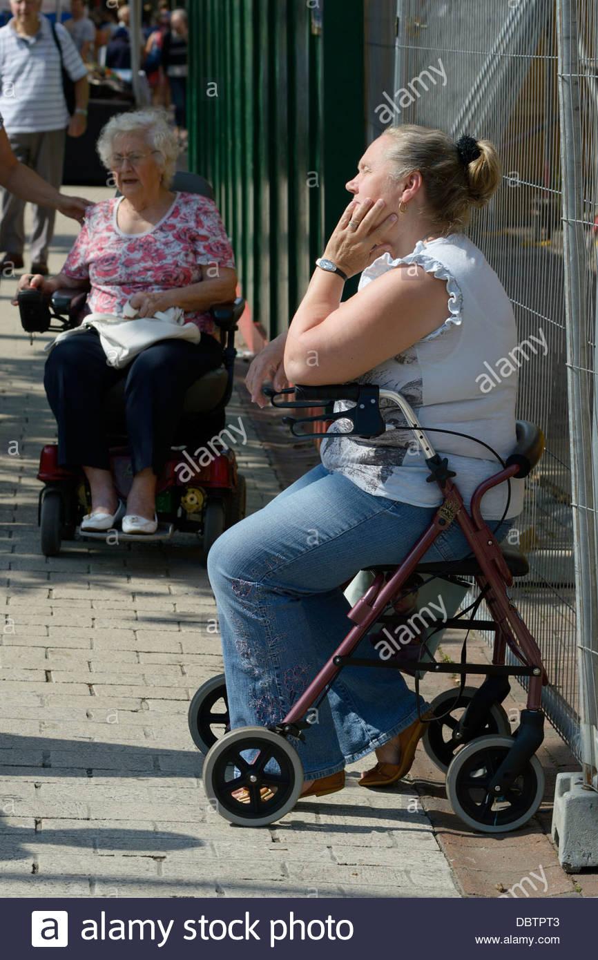 Une femme qui reste par assis sur une aide à la mobilité Photo Stock