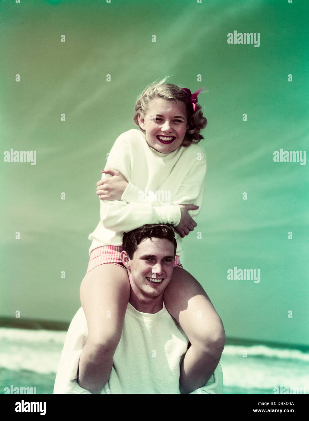 Années 1940 Années 1950 SMILING TEEN COUPLE AT BEACH GIRL SITTING ON BOYS ÉPAULES LOOKING AT CAMERA Photo Stock