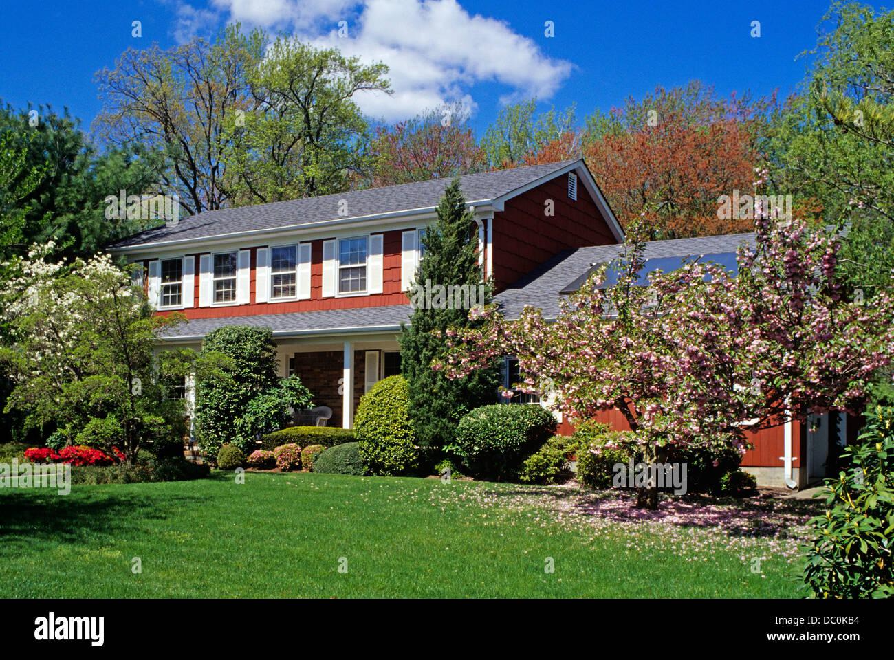 Des années 1990, maison rouge et buissons à fleurs au printemps Photo Stock