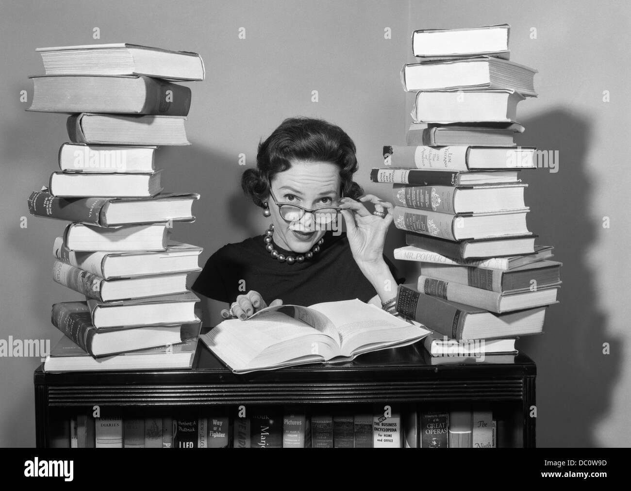1950 Femme assise ENTRE LES PILES DE LIVRES TIRANT DES LUNETTES POUR REGARDER AU-DESSUS DES JANTES Photo Stock