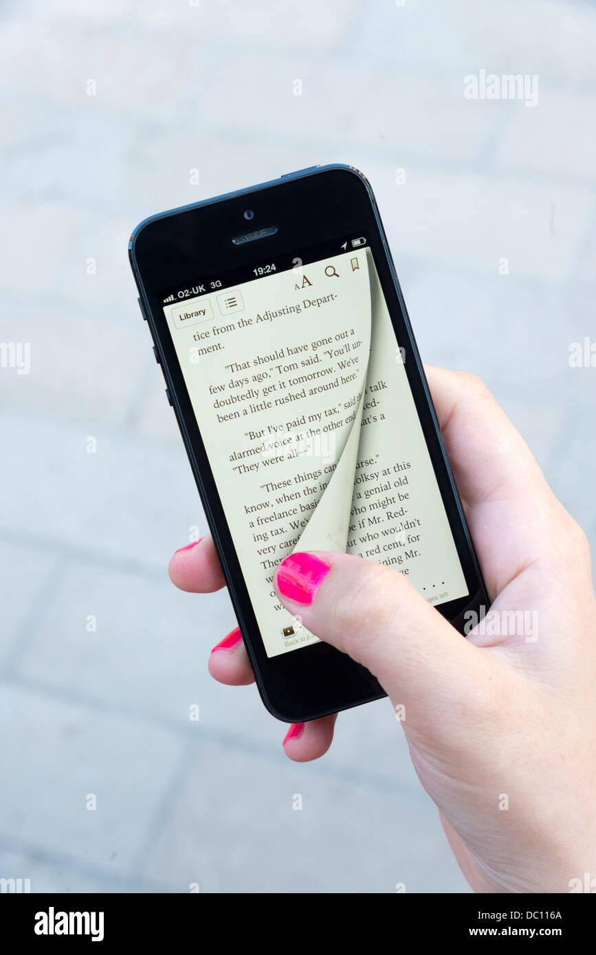 Femme tournant la page virtuelle d'un ebook avec l'app Apple iBooks sur iPhone 5 Banque D'Images