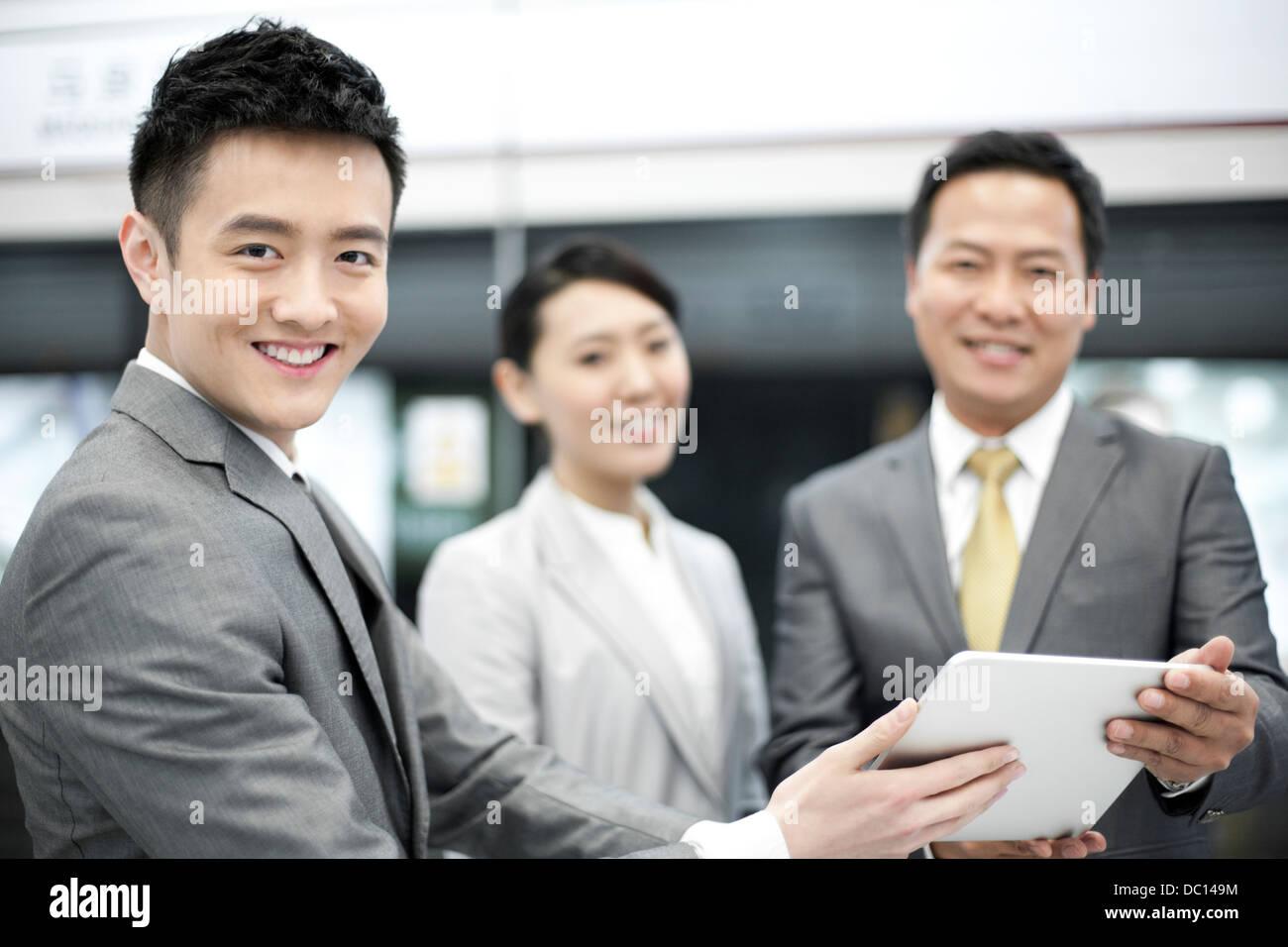 Les personnes gaies avec tablette numérique sur plate-forme du métro Banque D'Images