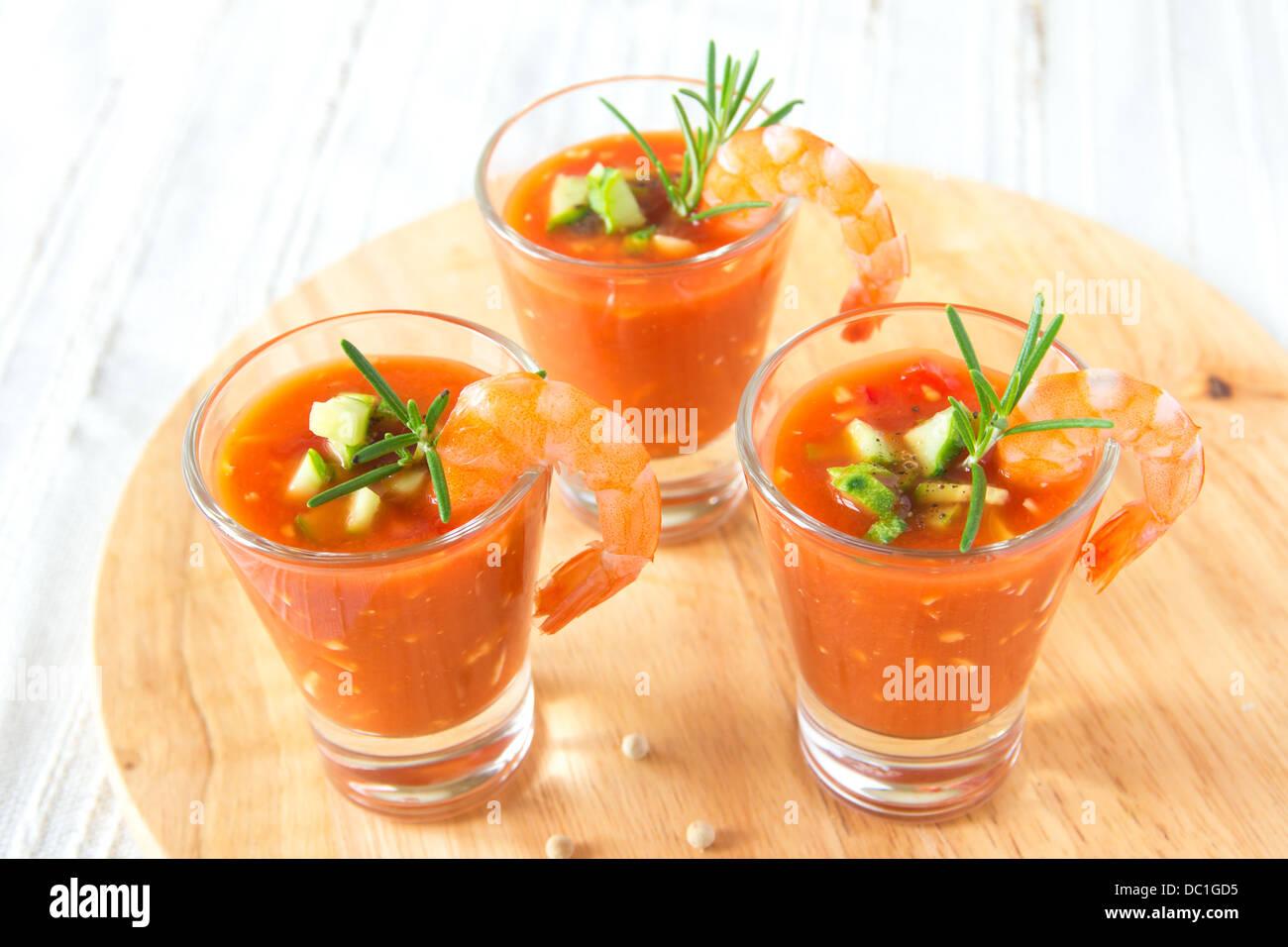 Délicieux froid frais savoureux gaspacho soupe aux tomates en partie lunettes avec les crevettes sur planche Photo Stock