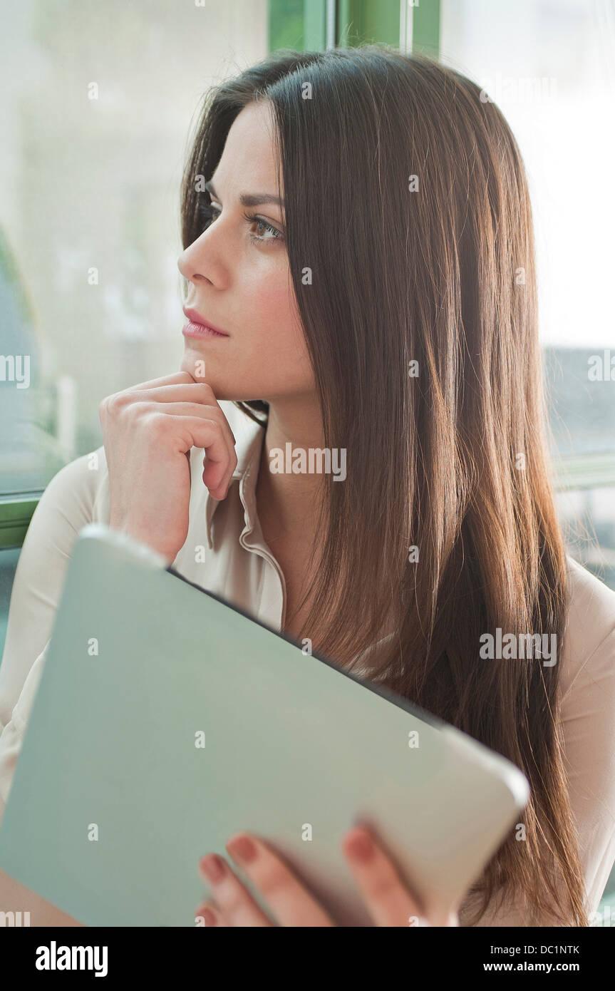 Jeune femme en poste à la fenêtre de Banque D'Images