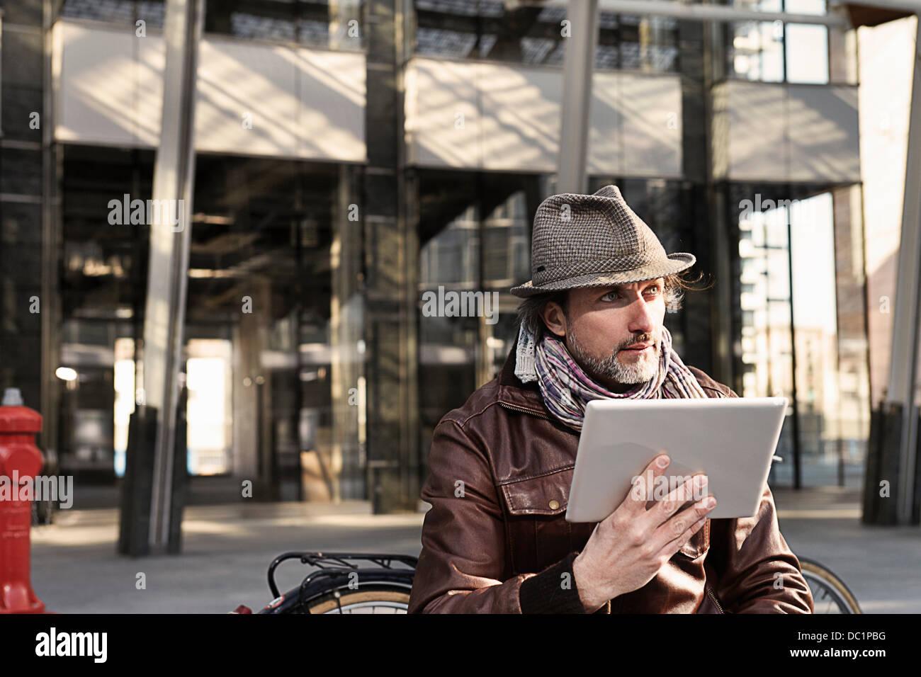 Mid adult man using digital tablet et à l'écart Photo Stock