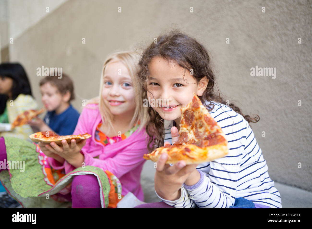 Petit groupe d'enfants eating pizza outdoors Photo Stock