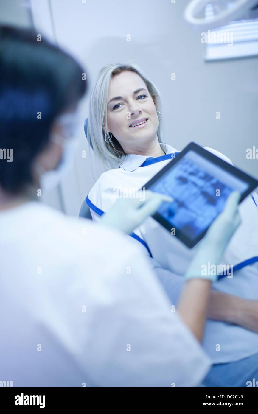 Dentiste à l'aide d'un écran tactile sur tablette numérique Photo Stock