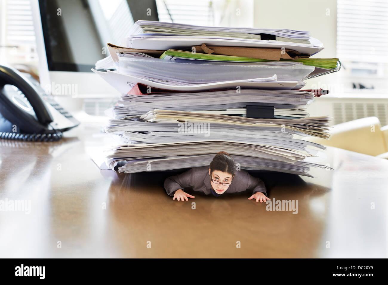 Businesswoman piégé sous la pile de documents volumineux sur un immense bureau, portrait Photo Stock