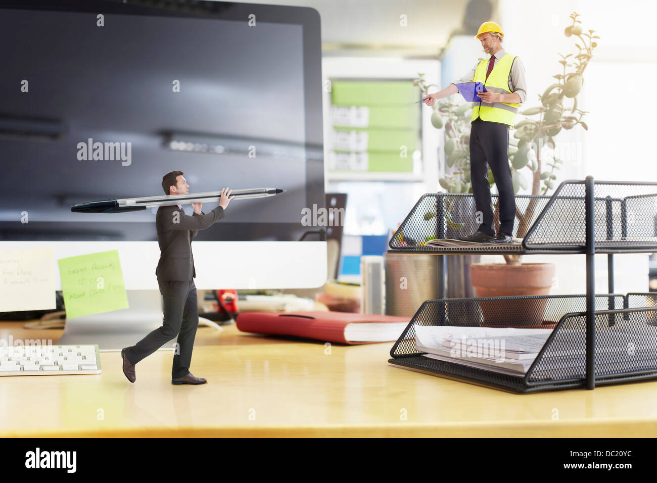 Contremaître diriger mature businessman carrying large stylo sur un immense bureau Photo Stock