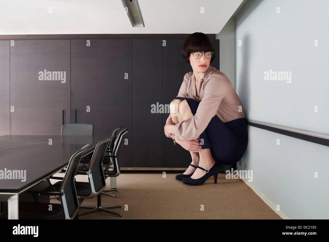 Woman crouching en petite salle de conférence Photo Stock
