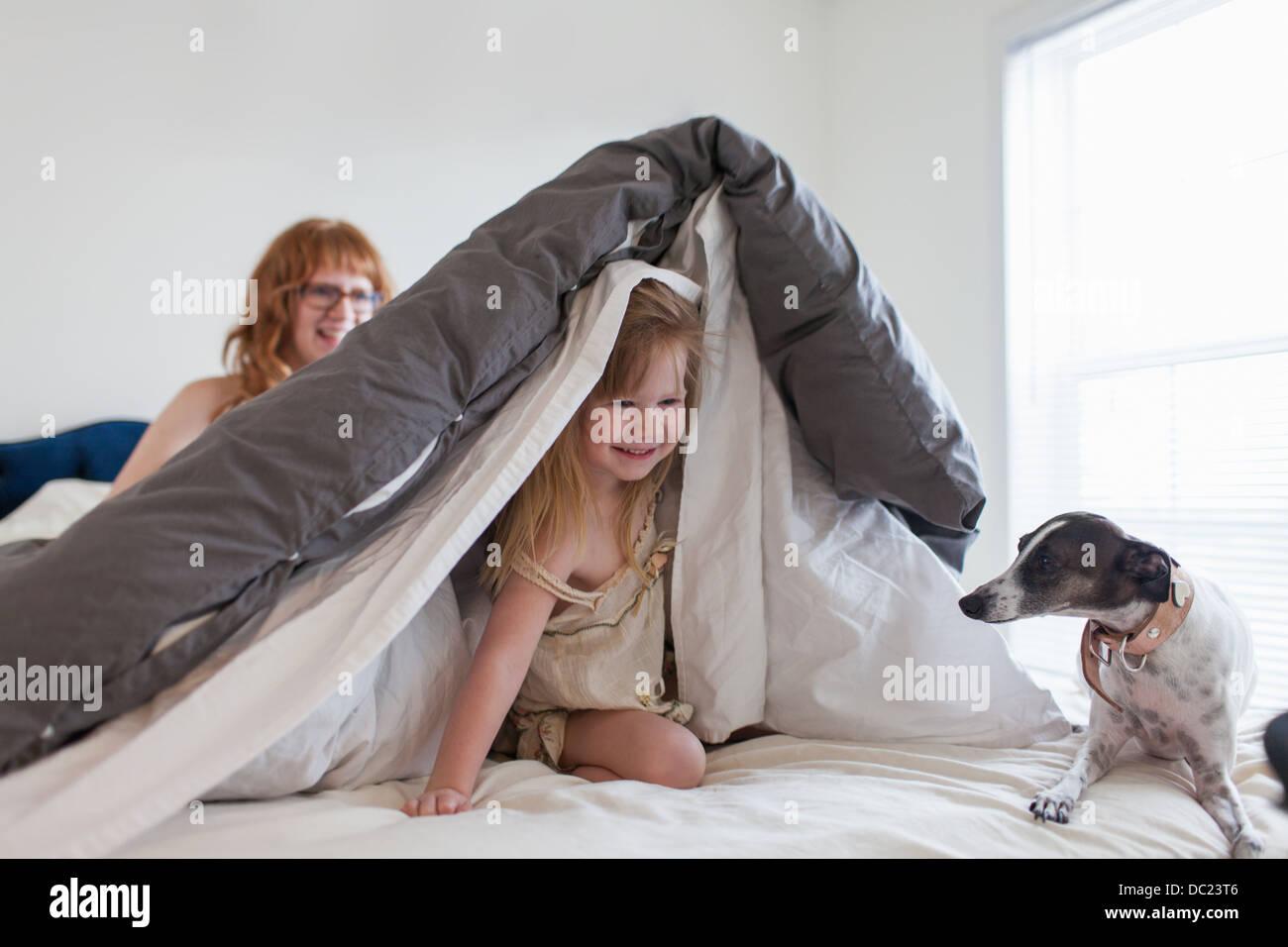 Fille de se cacher sous une couette, mère et dog on bed Photo Stock