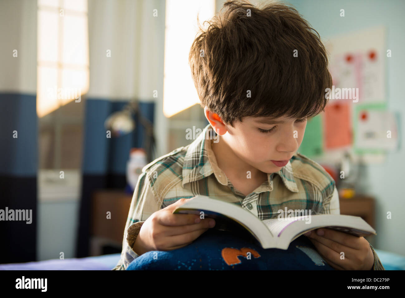 Boy sitting on bed reading book Photo Stock