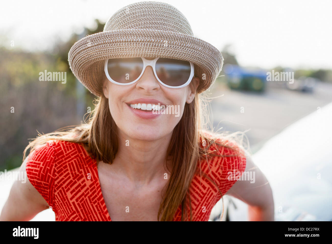 Young woman wearing Sunglasses and sunhat smiling towards camera Photo Stock