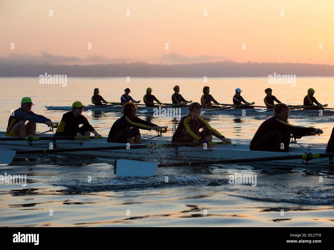 Quatorze personnes aviron au coucher du soleil Photo Stock
