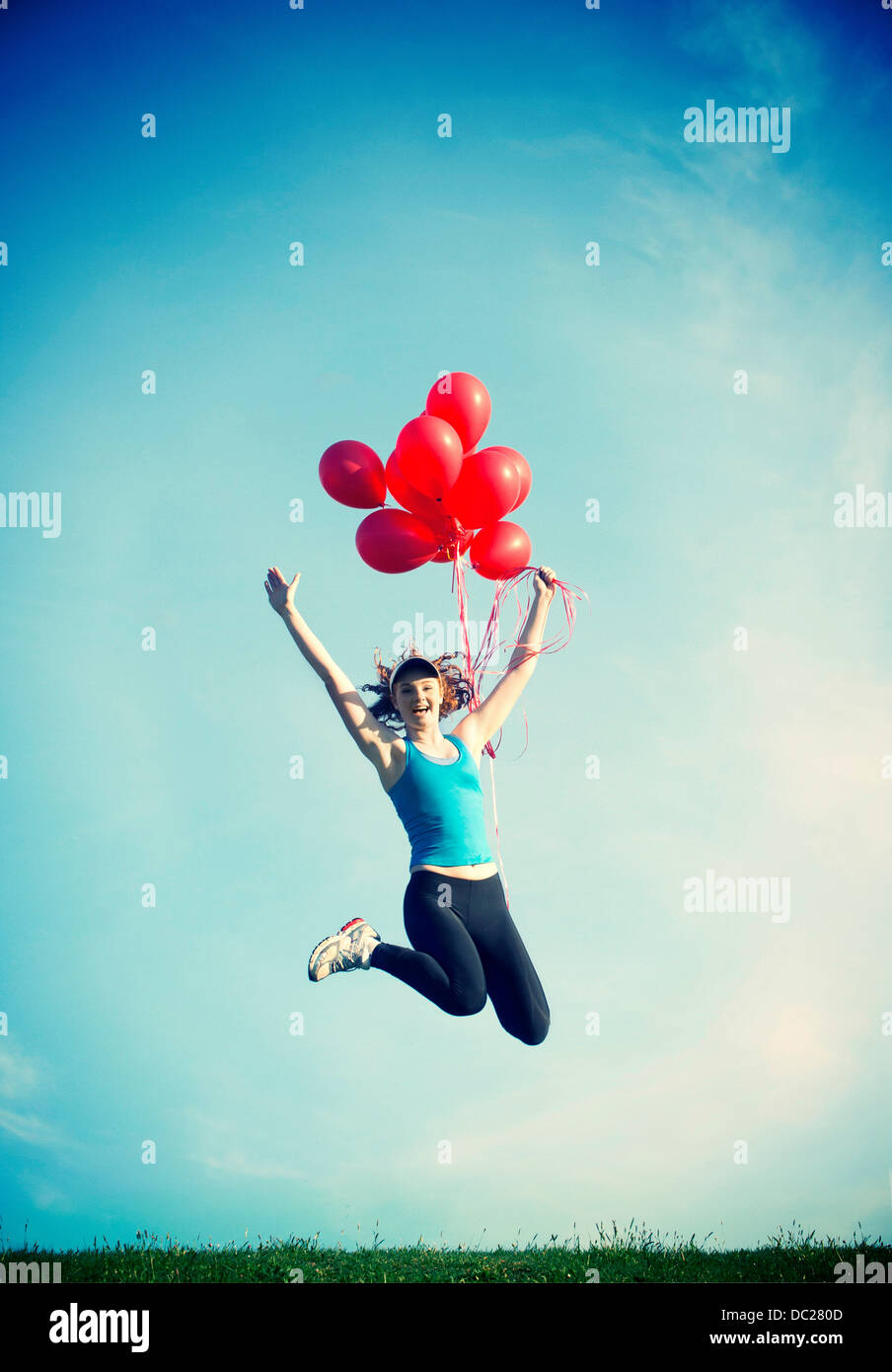 Teenage girl jumping in mid air holding red balloons Photo Stock