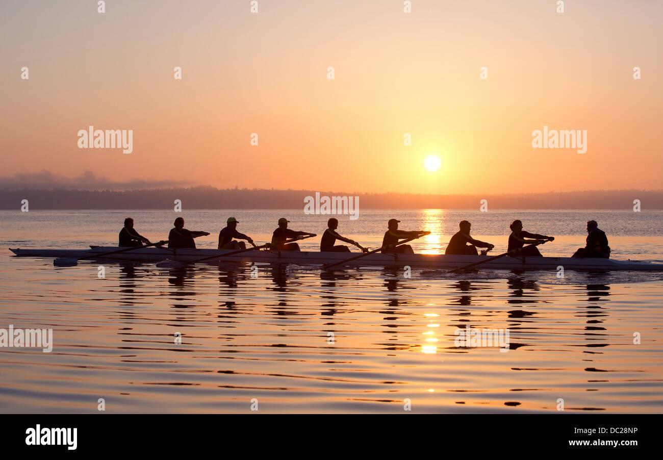 Neuf personnes aviron au coucher du soleil Photo Stock