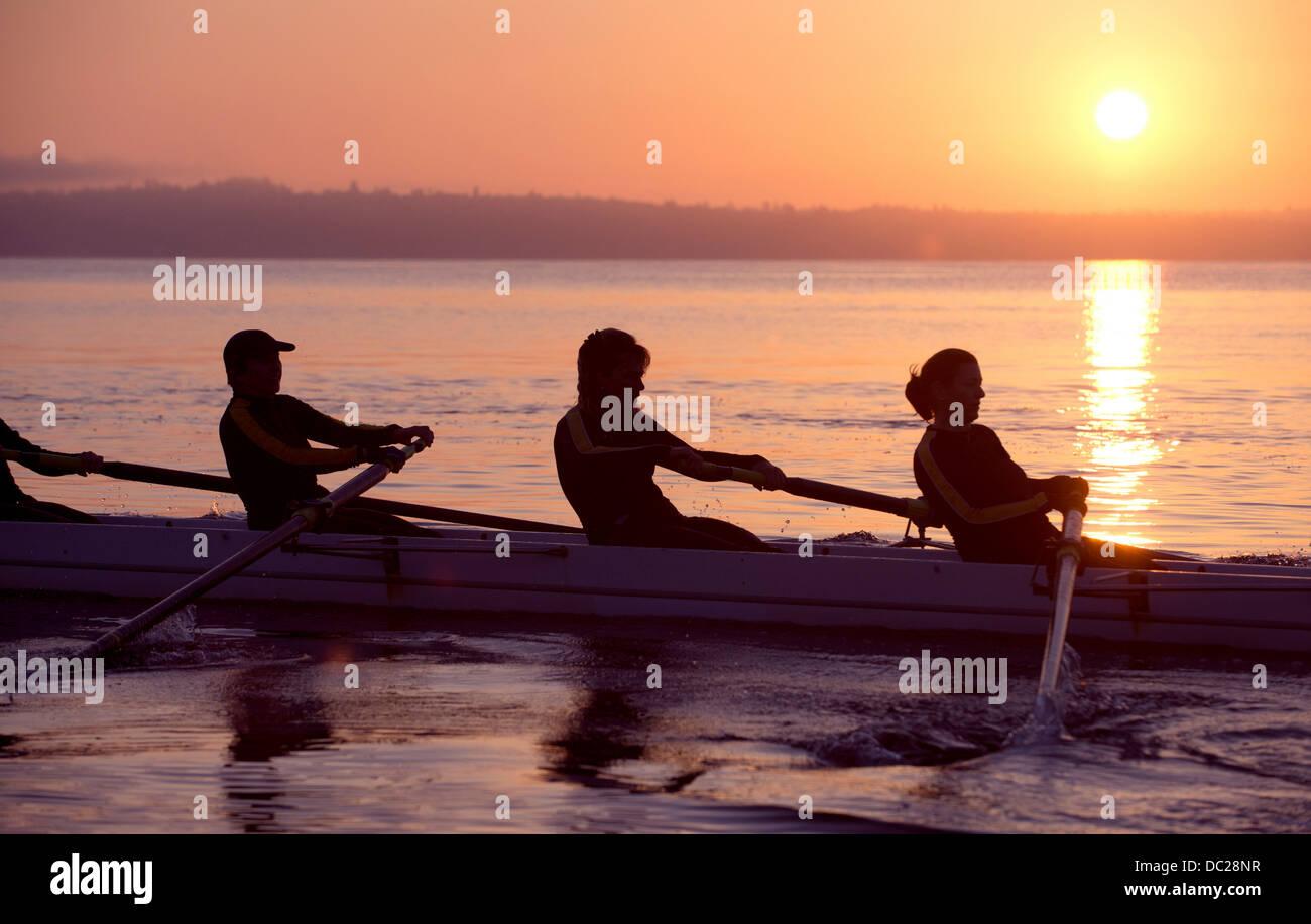 Quatre personnes aviron au coucher du soleil Photo Stock