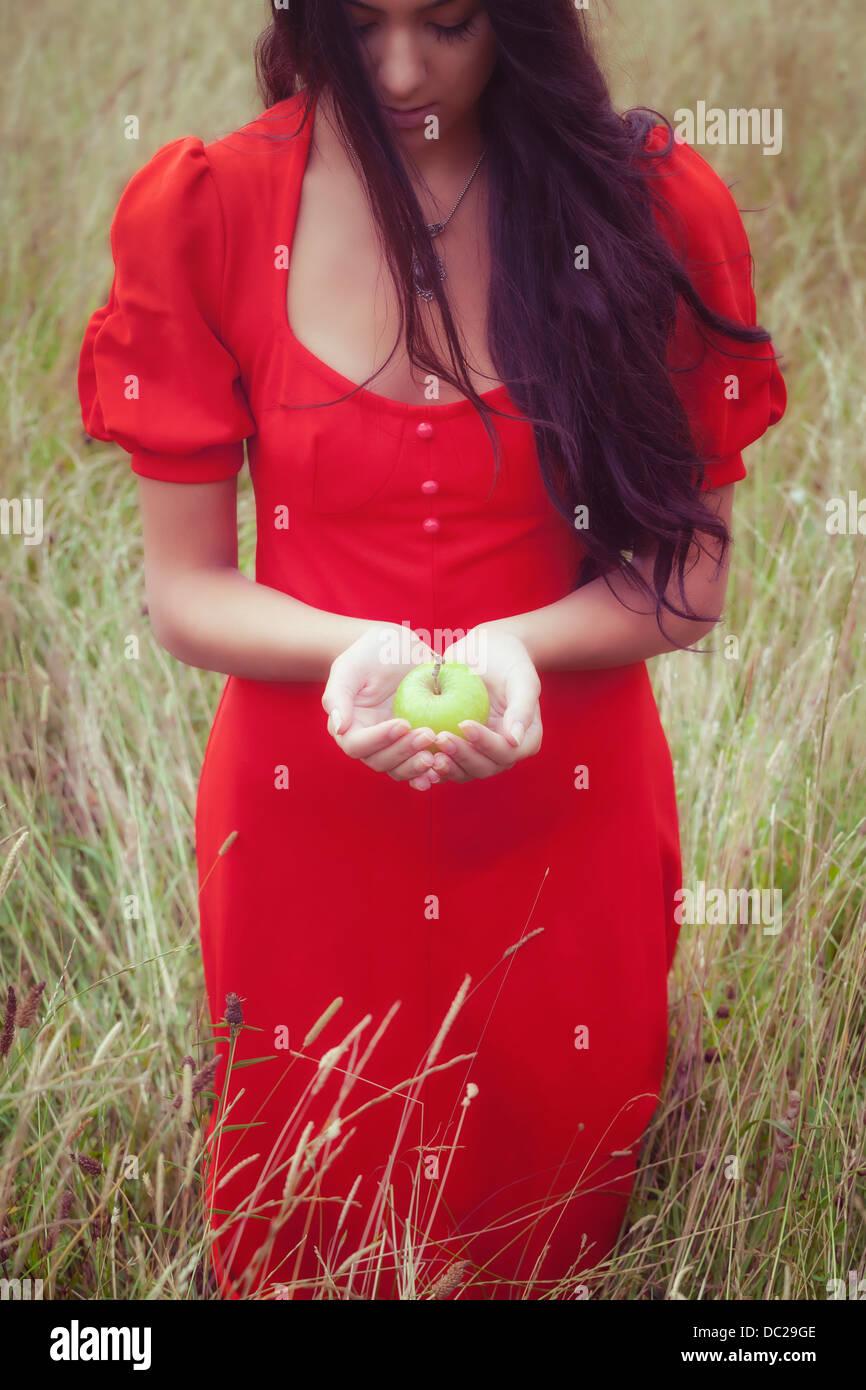 Une femme dans une robe rouge, tenant une pomme verte Photo Stock