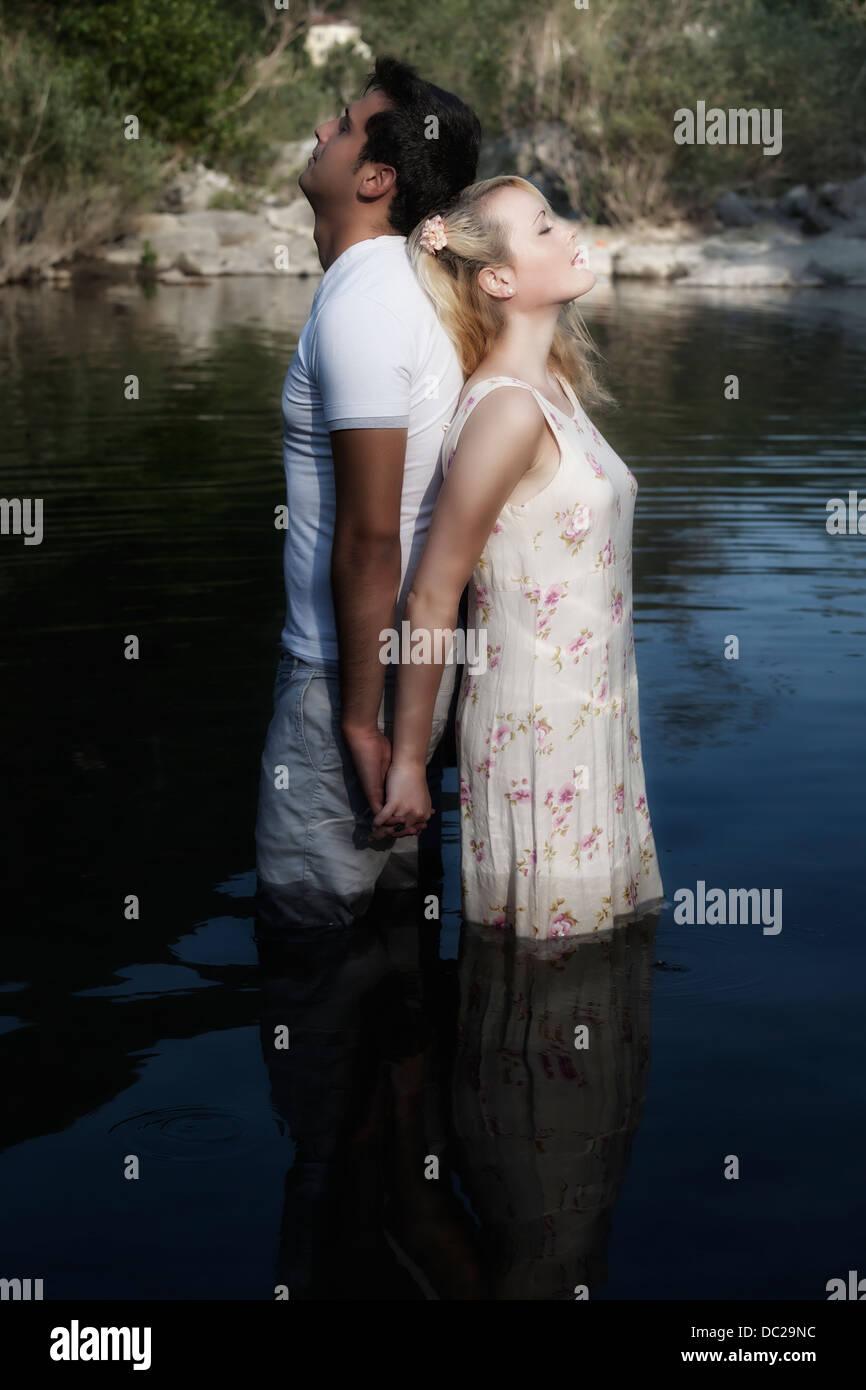 Un couple dans l'eau, dos à dos Photo Stock