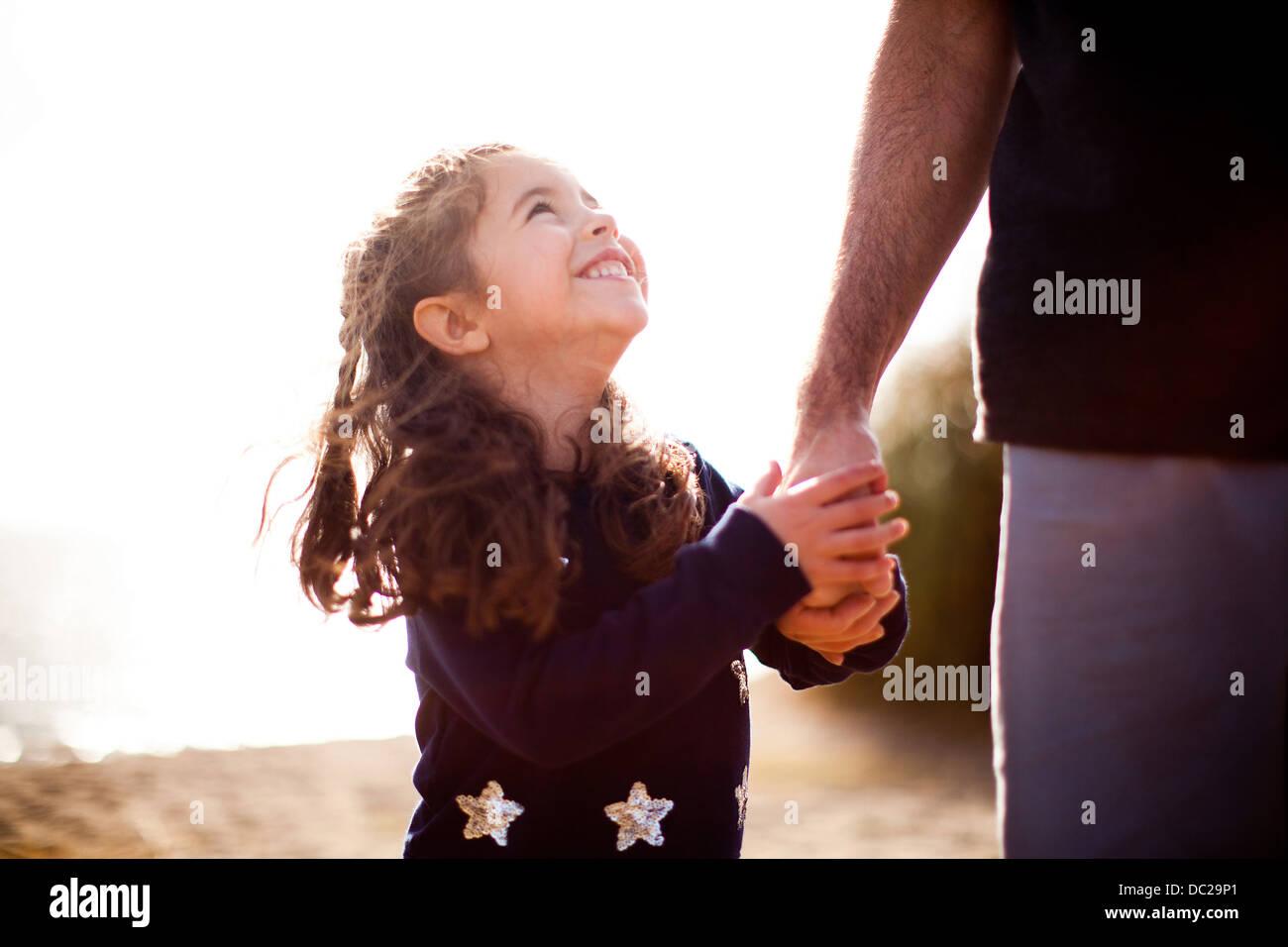 Girl holding main du père, jusqu'à Banque D'Images