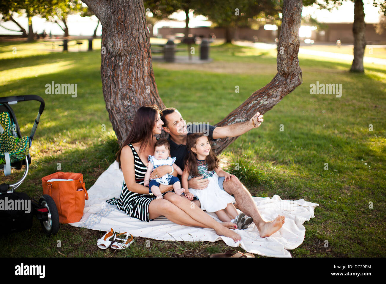 Famille avec deux enfants assis on picnic blanket Photo Stock