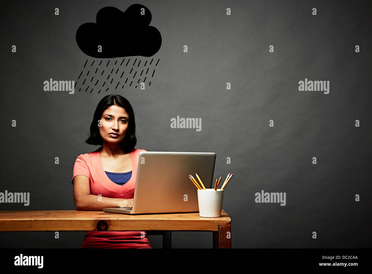 Femme assise sous nuage de pluie sombre Photo Stock