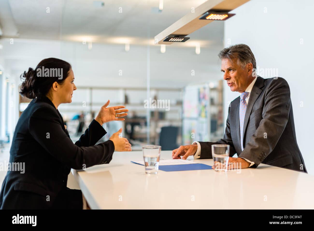 Recruteur (homme d'affaires d'âge moyen) contrôle du candidat, une jolie jeune femme,lors de l'entretien Photo Stock