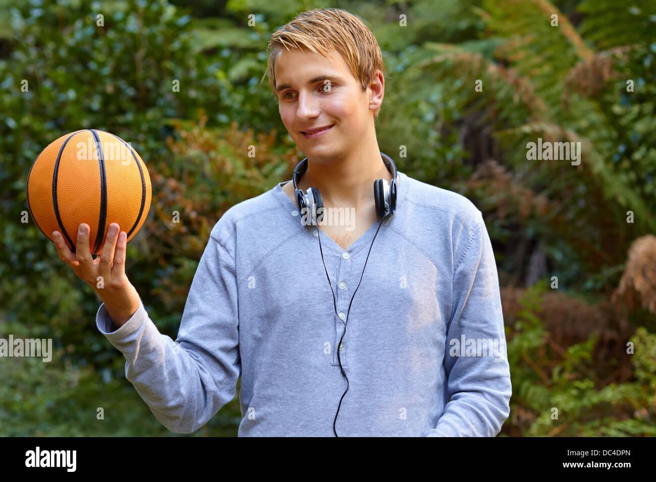 Jeune homme qui envisage un terrain de basketball sports Photo Stock