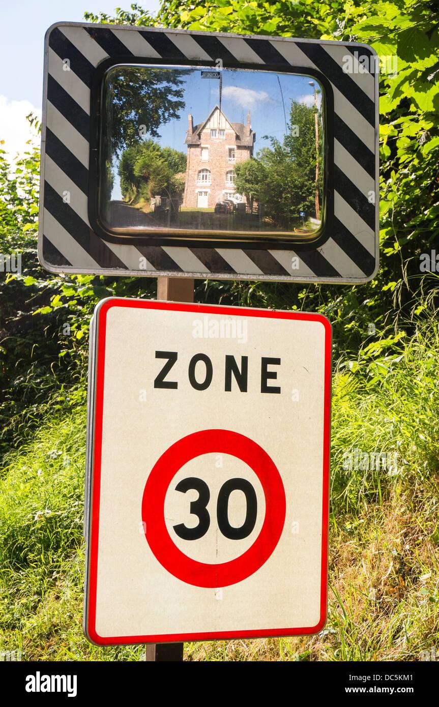 Une limitation de vitesse signer avec une grande maison à Clécy (réflexion dans le département Photo Stock