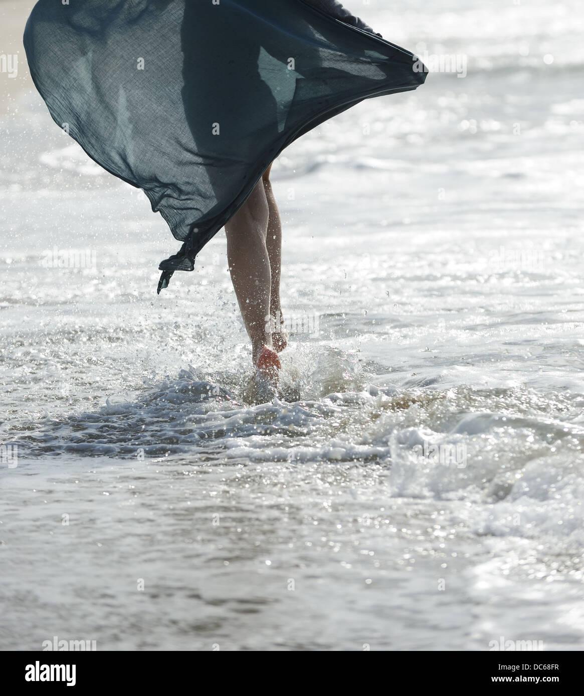 Une jeune femme marche sur la mer Photo Stock