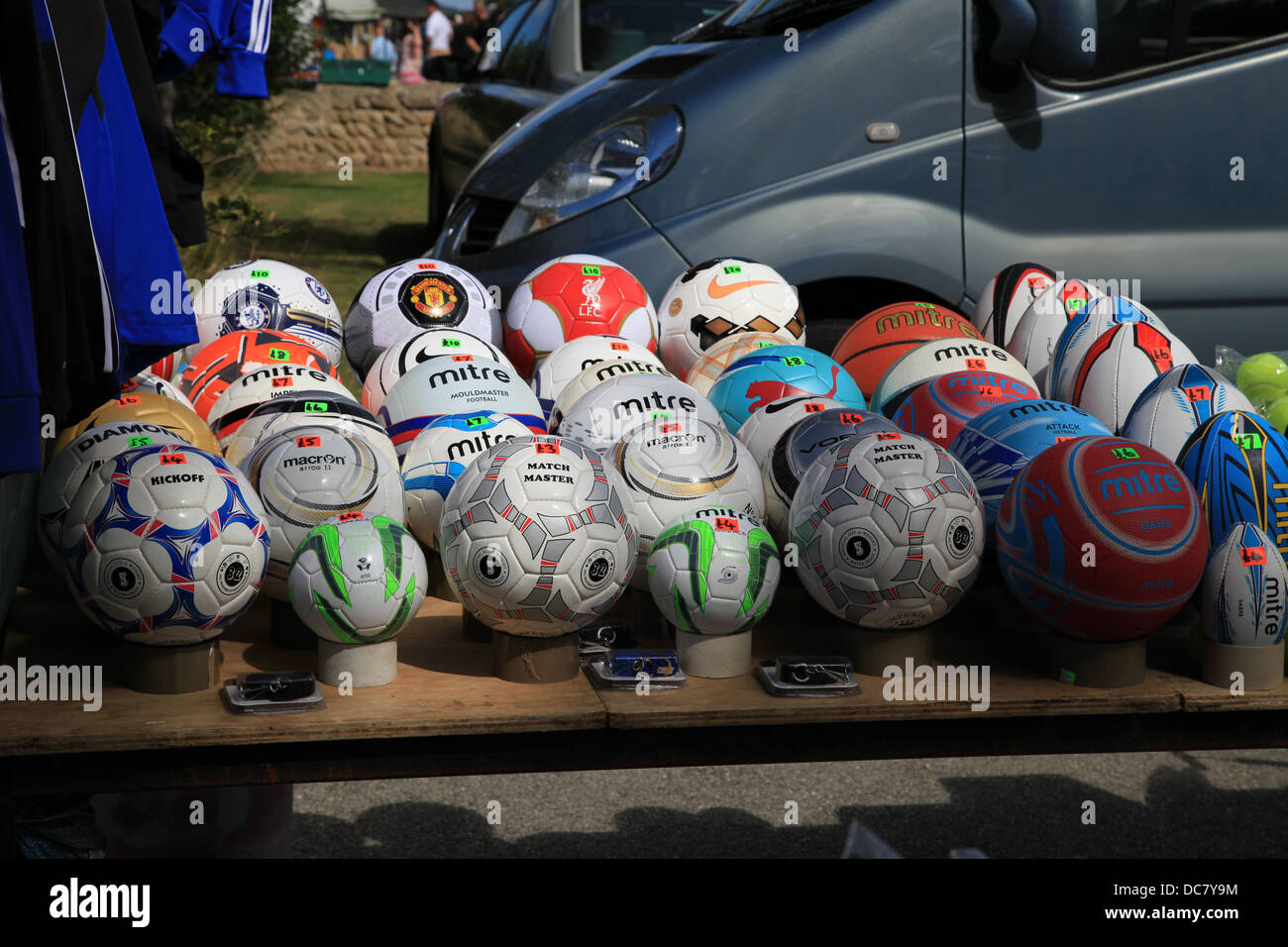 Des ballons de football et rugby à la vente à un décrochage du marché. Banque D'Images