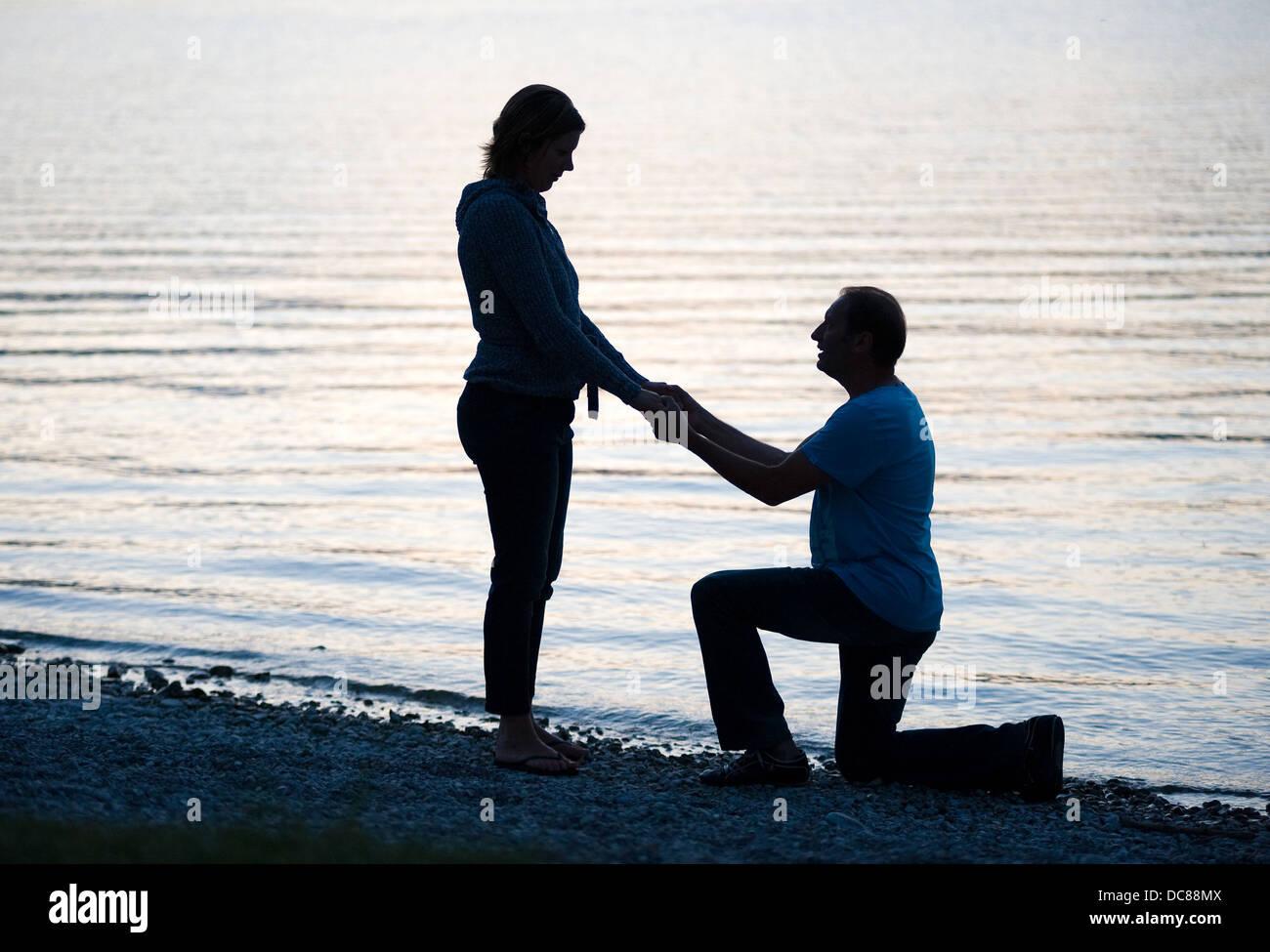 Un homme est en train de faire une demande en mariage à sa petite amie Photo Stock