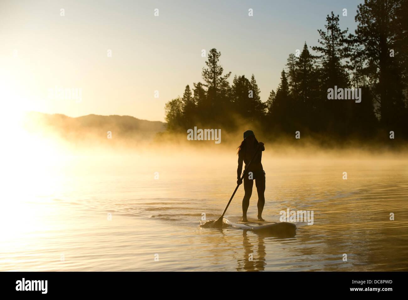 Une femme, se profile Stand Up Paddleboarding (SUP) au lever du soleil dans la brume au lac Tahoe, CA. Photo Stock