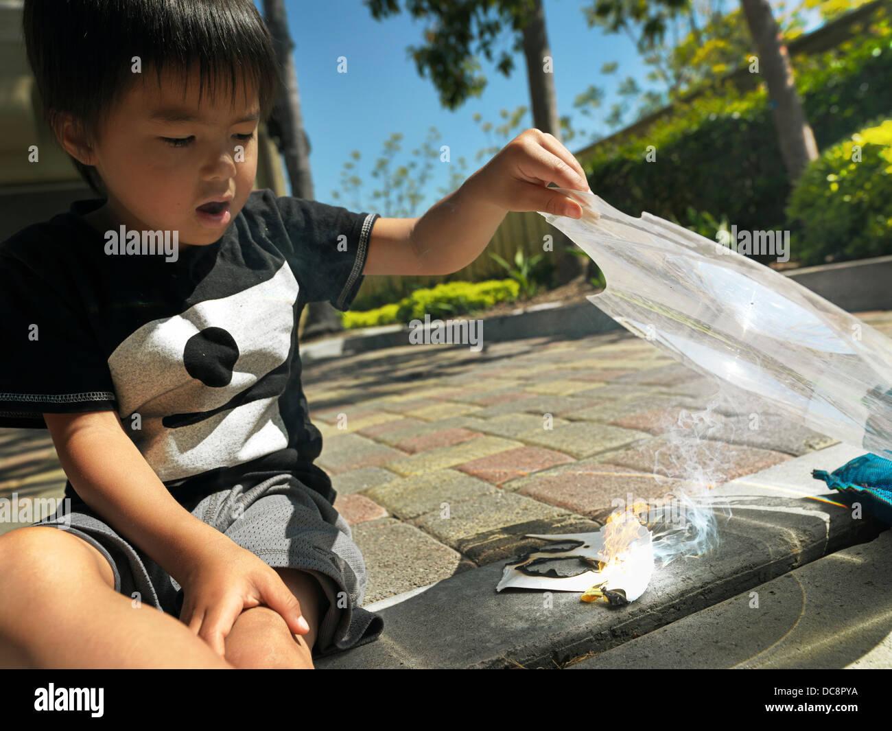 Kid faire feu avec une loupe. Photo Stock