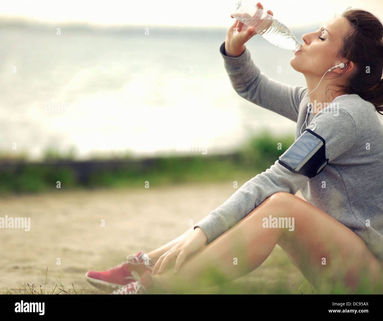 Coureuse assis sur l'herbe pendant que l'eau potable Banque D'Images
