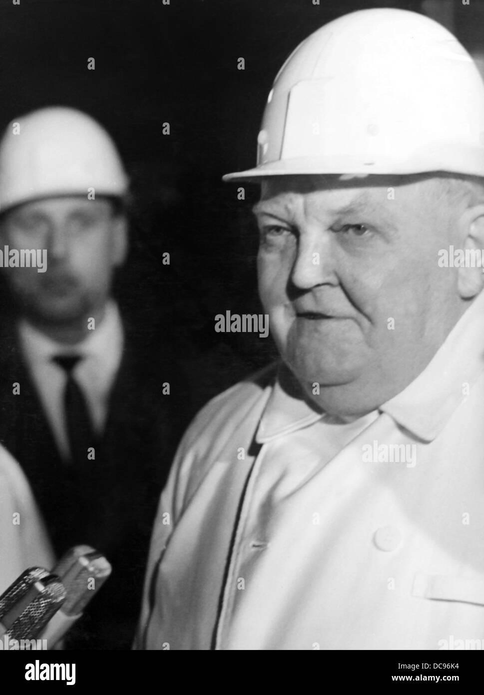 Chancelier Ludwig Erhard porte un casque de sécurité et les vêtements des mineurs pendant une visite à la mine de charbon dans la région de Herne le 2 avril en 1965. Banque D'Images