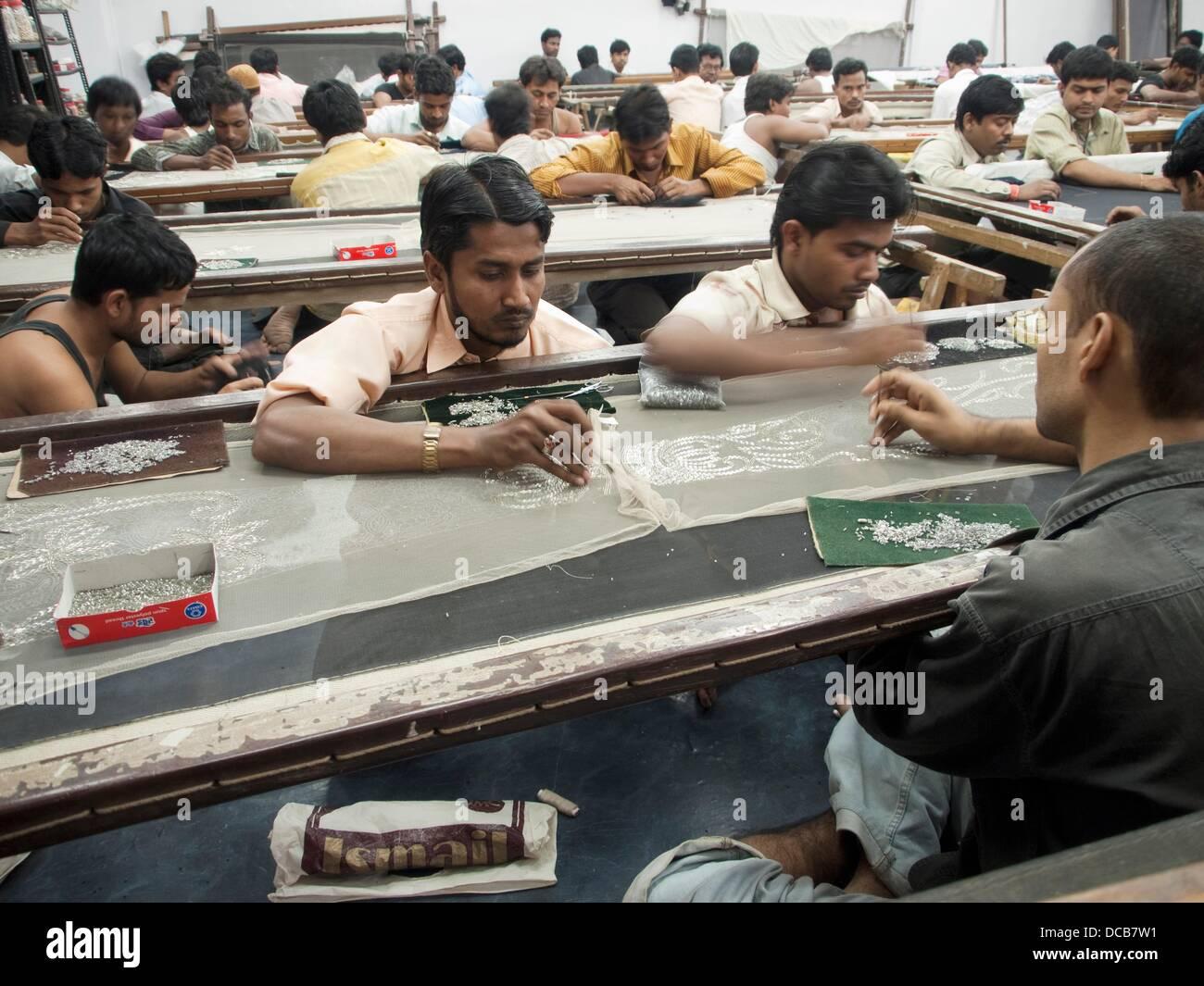 Les ouvriers placent et coudre des perles et des embellissements sur un tissu dans le Mumbai, Inde atelier/bureau Banque D'Images