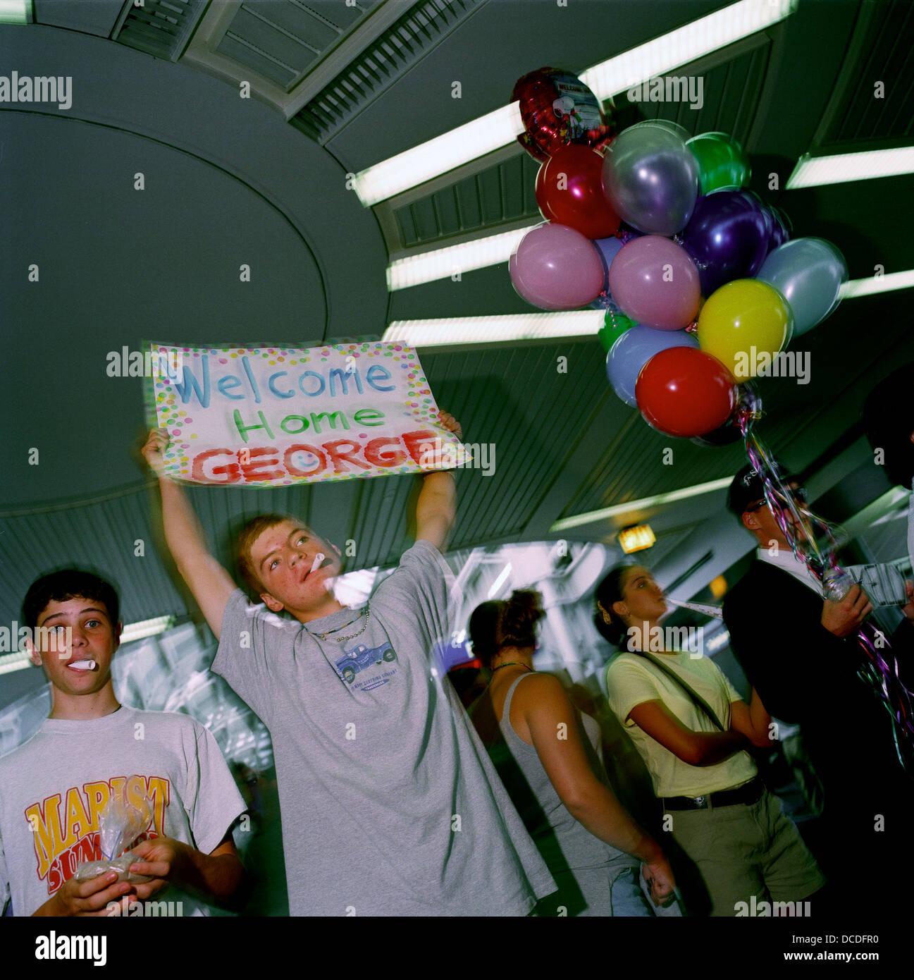 Avec d'autres, un jeune homme avec un ballon Accueil Bienvenue répond à un ami appelé George après une longue absence, Banque D'Images