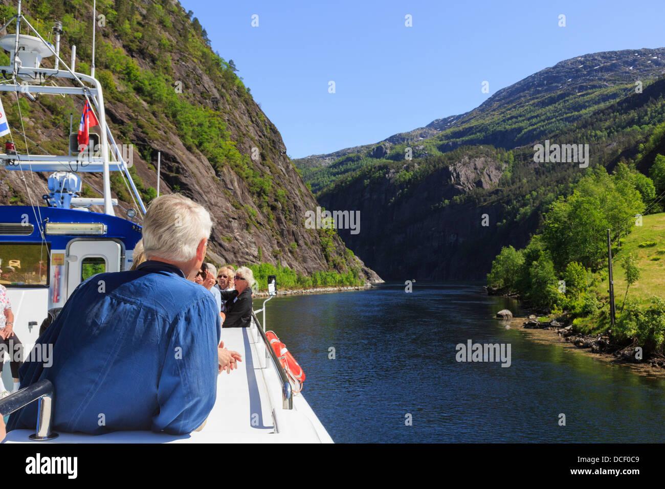 Les touristes sur le pont d'un bateau de croisière naviguant le long Mostraumen Mofjorden étroit de Photo Stock