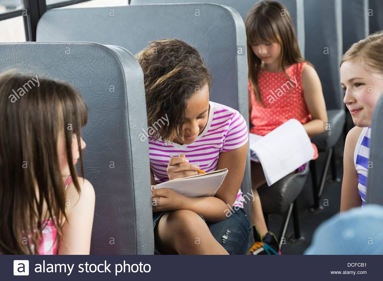 Ecolières bus assis à l'intérieur Photo Stock
