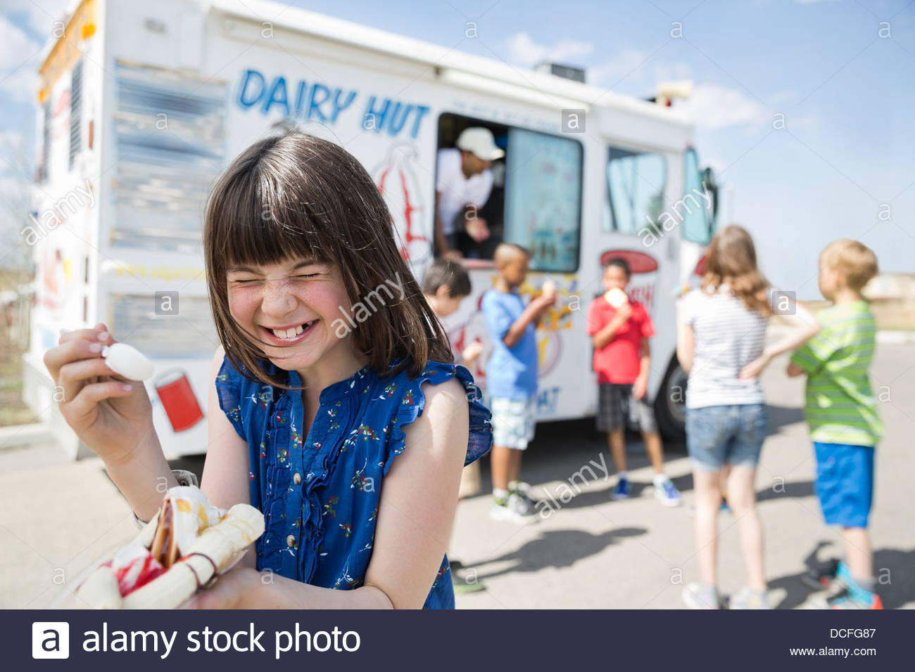 Girl laughing while eating banana split Photo Stock