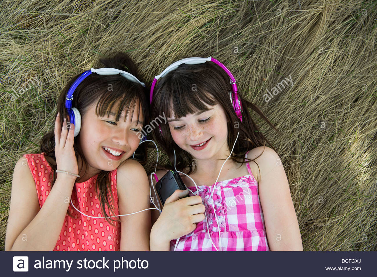 Les filles se coucher listening to headphones Photo Stock